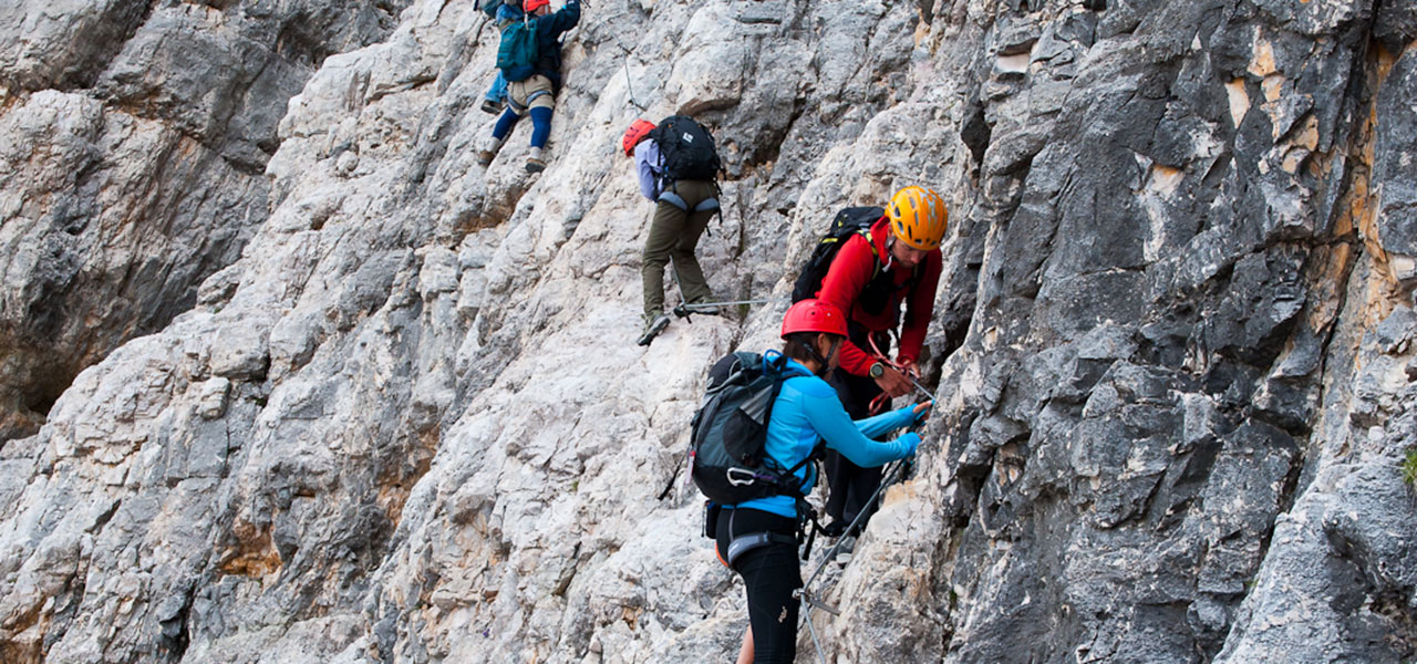 Group of climbers securing themselves on a via ferrata