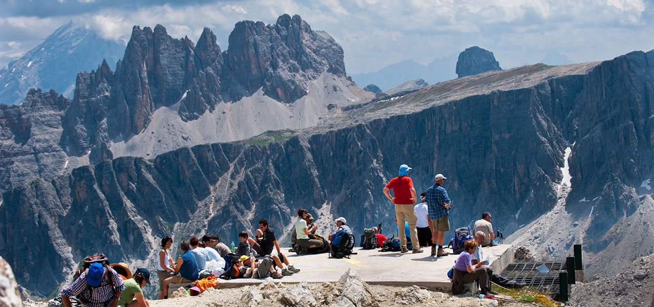 Group of hikers resting in front of the Dolomites