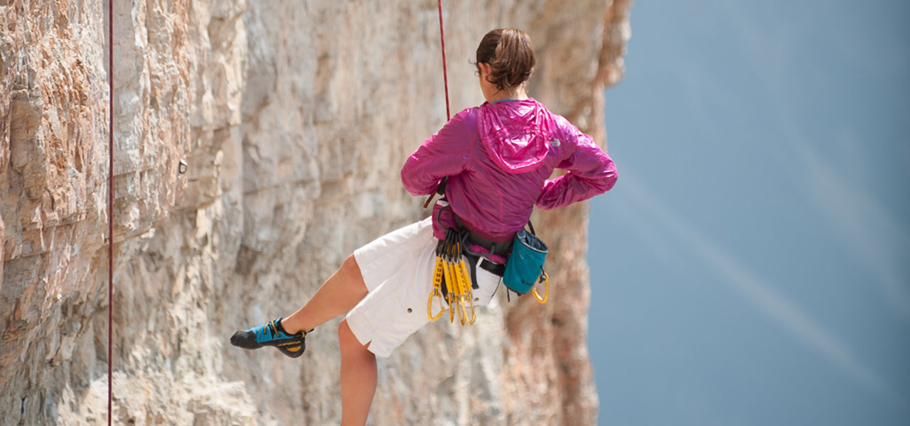 Woman hanging on a climbing rope from a mountain wall