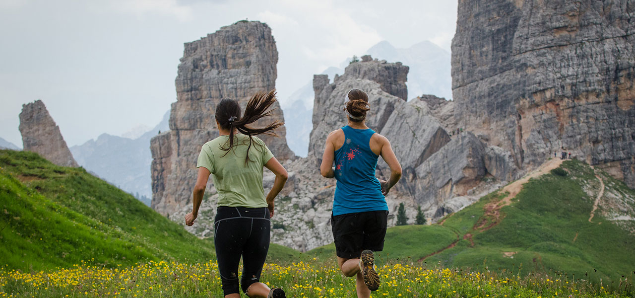 Two mountain runner on an Alpine pasture with Dolomites in the background