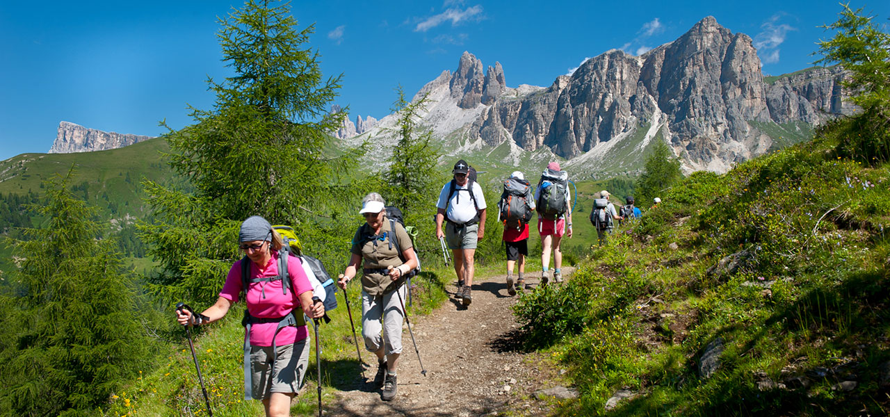 Hikers on a hiking path with Dolomites in the background