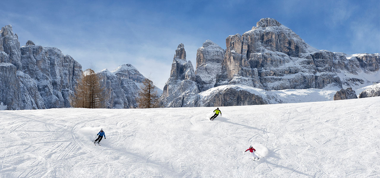 Skier on a slope in front of snowy Dolomites