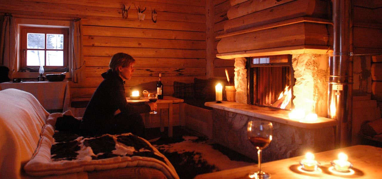 A glass of wine in front of the fire place