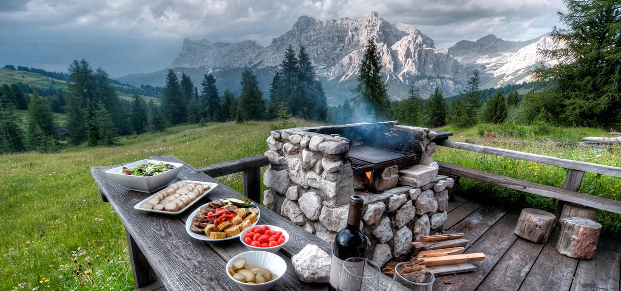 Vegetables and barbecue with woods and Dolomites in the background