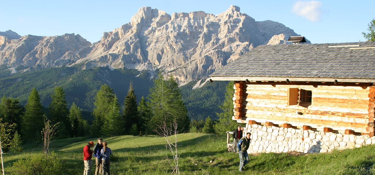 Sunrise at the mountain hut with people standing outside