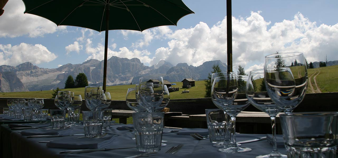 Glasses on set table with Dolomites in the background