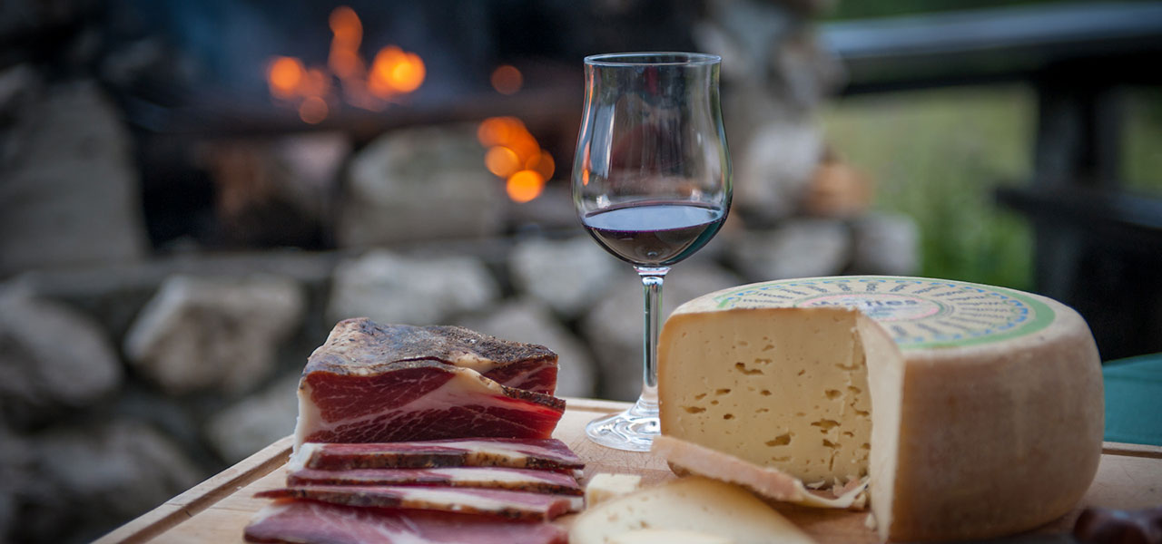 Speck, cheese and a glass of red wine on a wooden tray