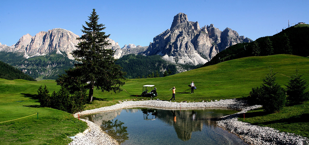 Golf course with lake, meadows and Dolomites