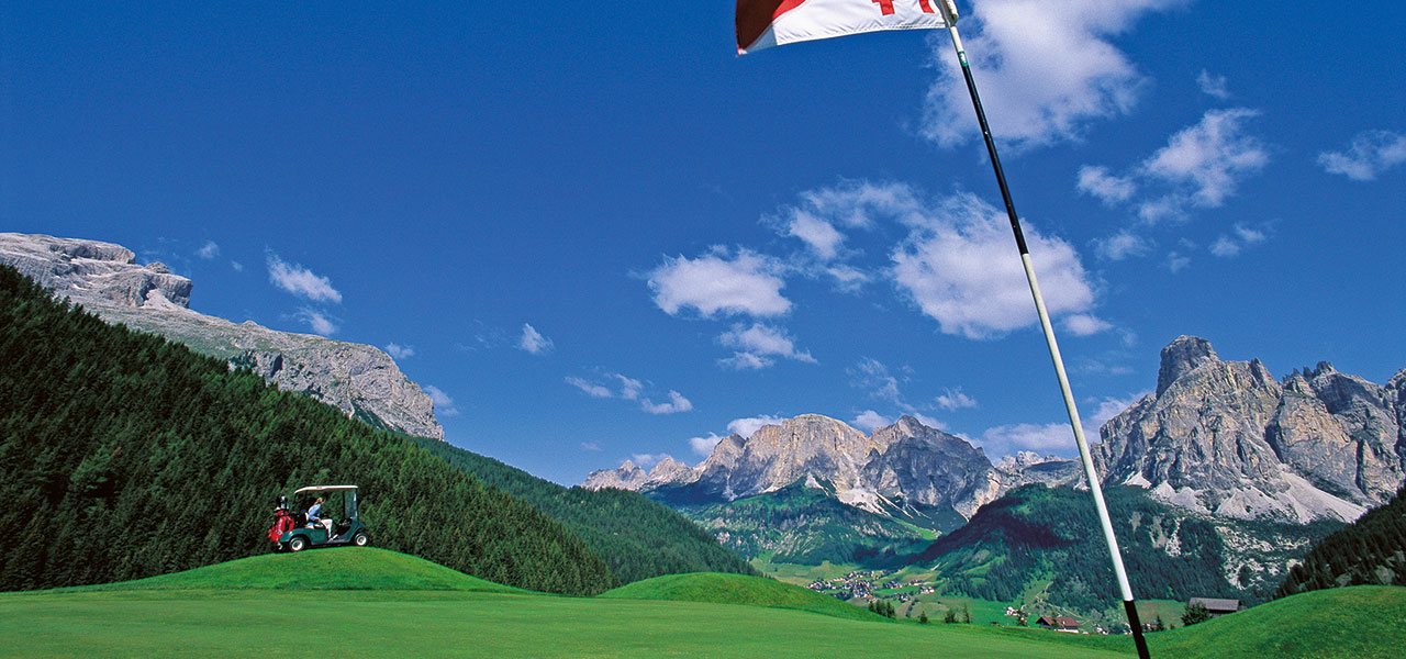 Golfcaddy on golf course with Dolomites