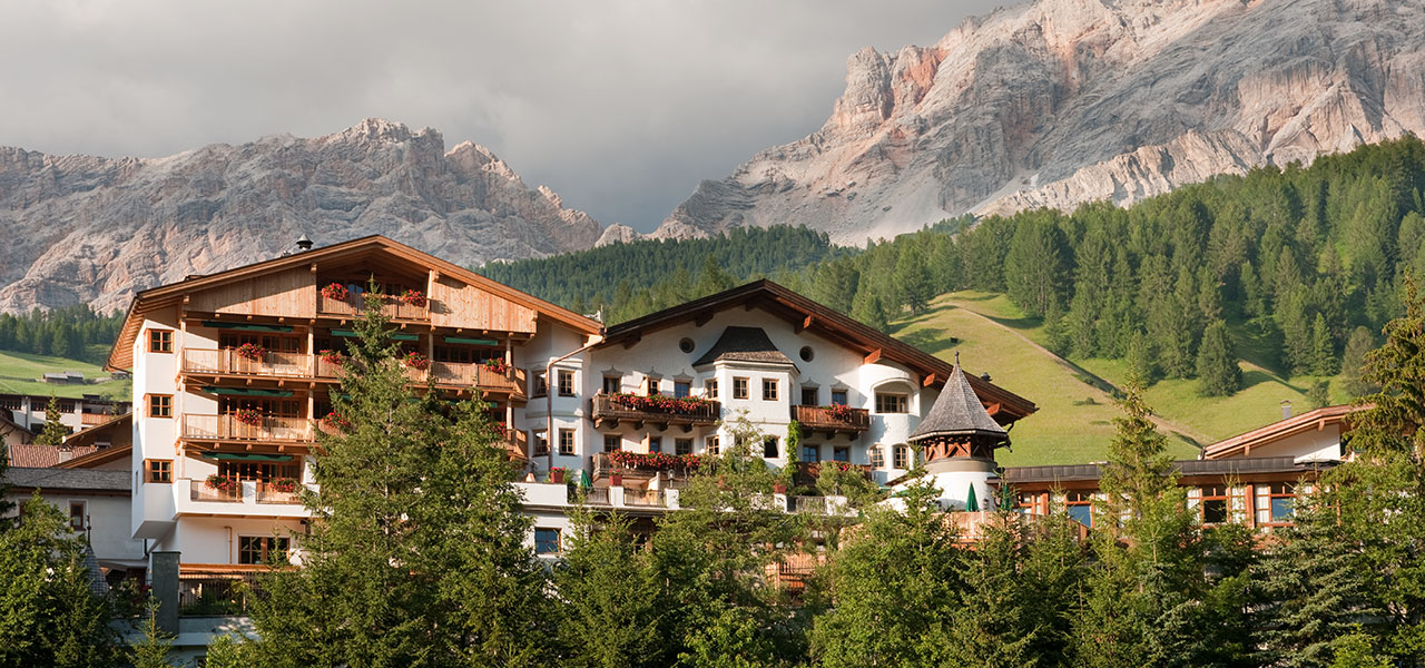 Exterior view of Hotel Rosa Alpina with Dolomites in the background