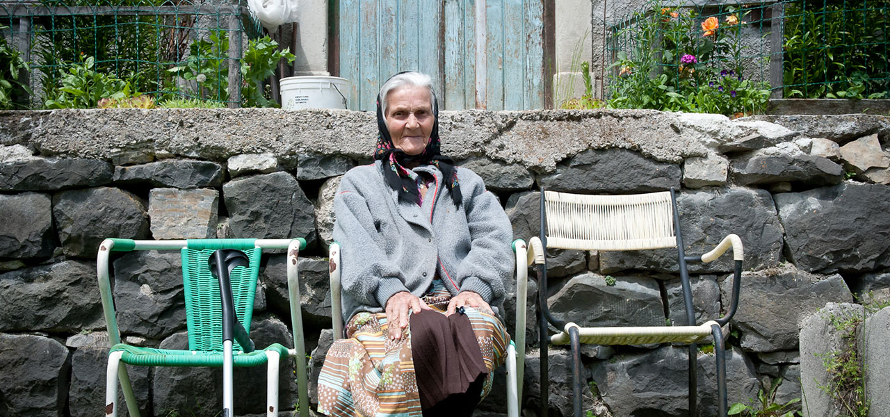 Woman sitting on chairs with stone wall in the background