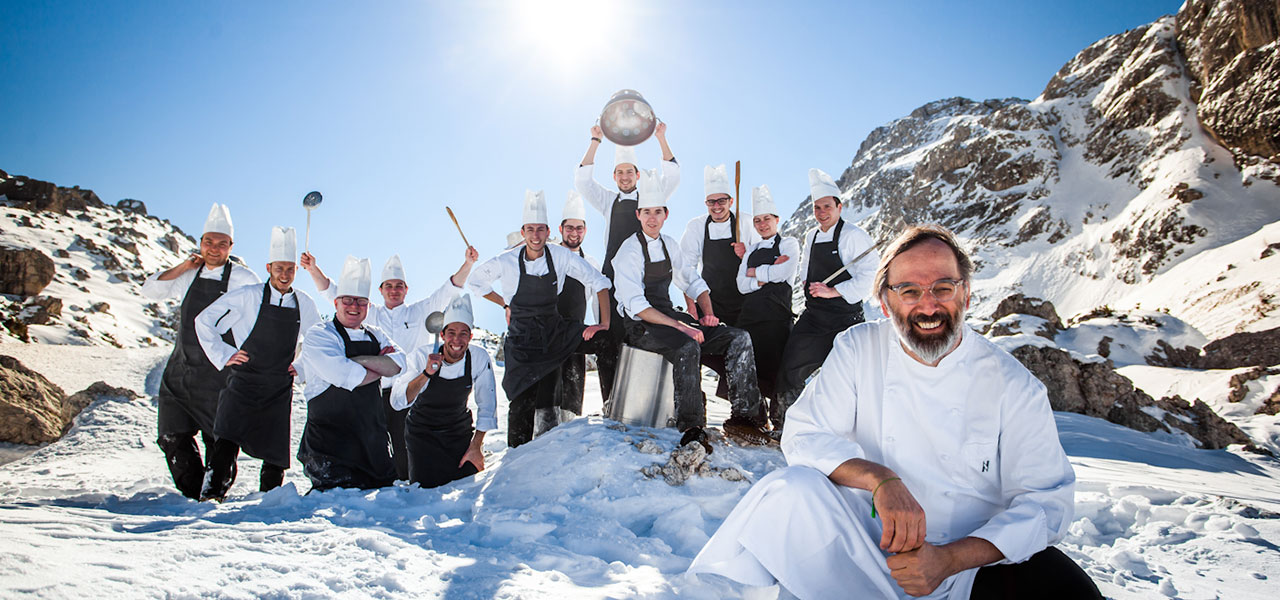 The kitchen team with pans and spoons on snowy mountains with Chef Niederkofler in the foreground