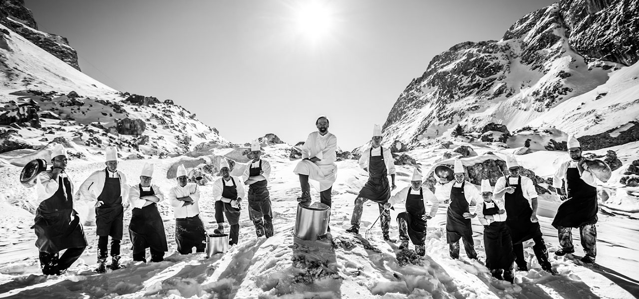 Chef Norbert Niederkofler and his kitchen team on a snowy peak