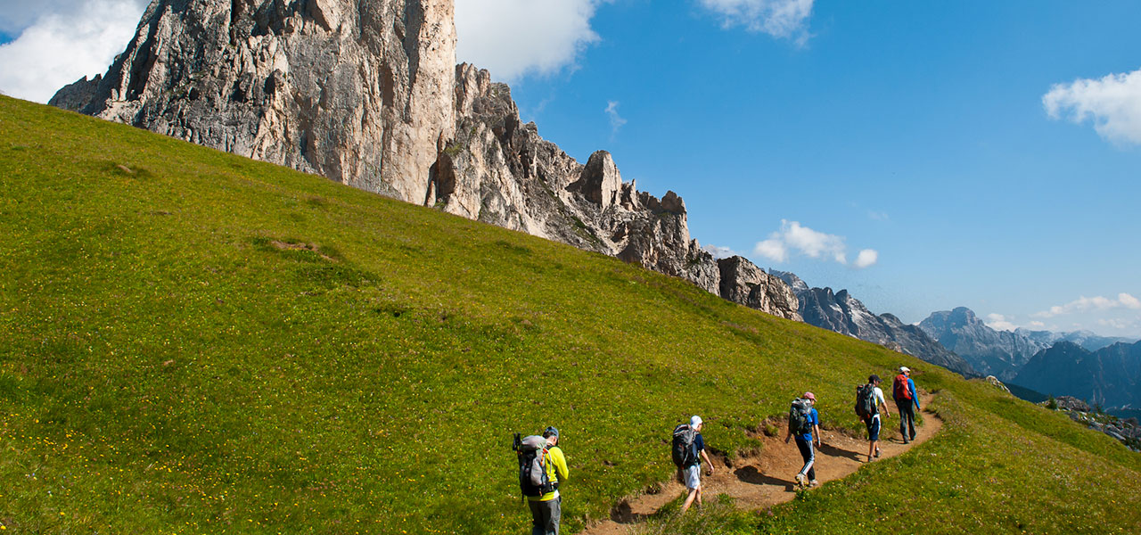 Hikers on mountain path with Dolomites in the background