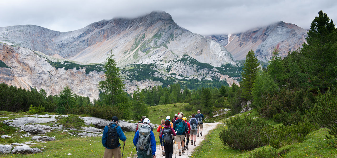 Hiking group on mountain path with Dolomites in the background