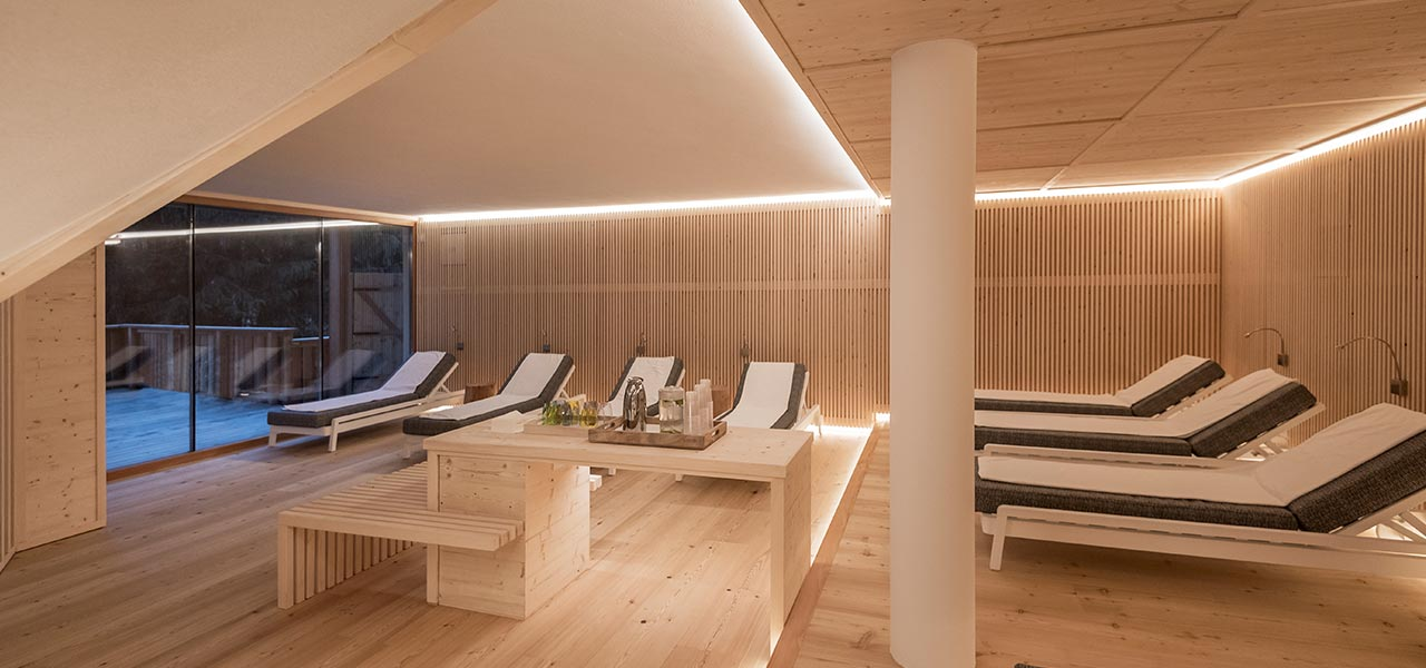 Relax room in natural wood with sun beds and a table with a tray of teas