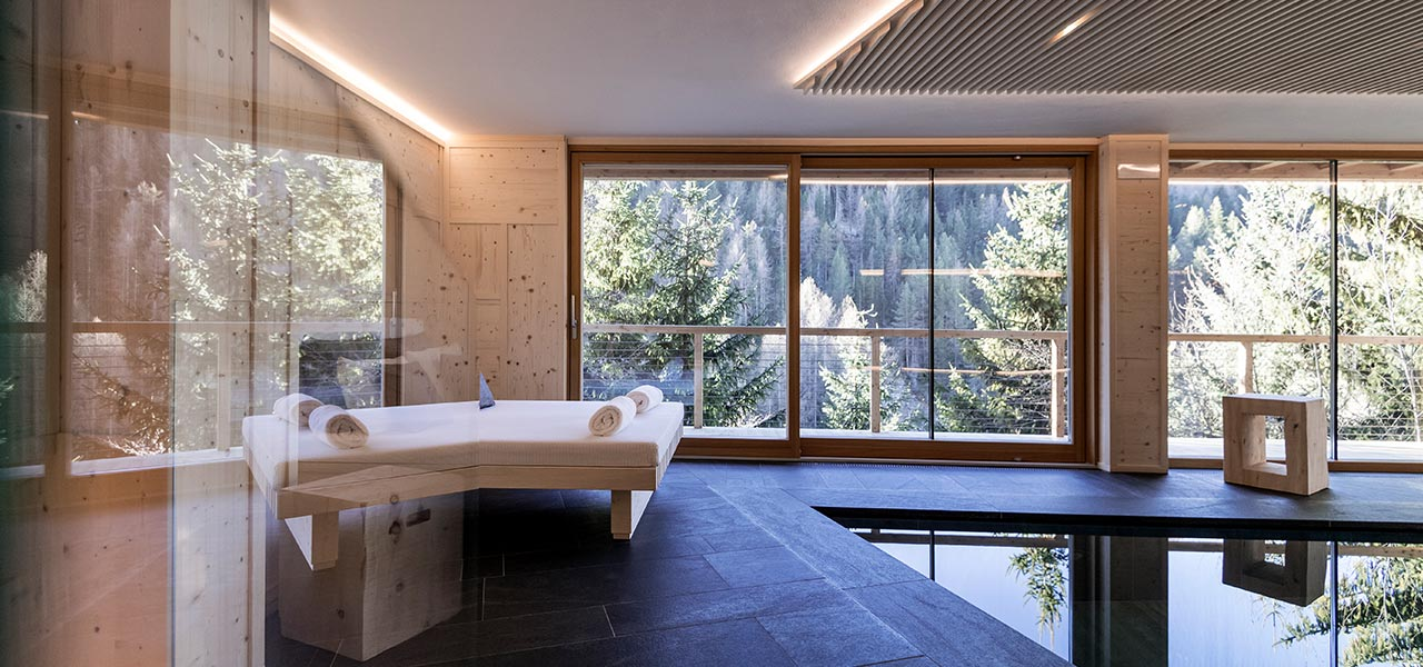 Glass windows in the wellness area with swimming pool and comfort zone overlooking the woods of San Cassiano