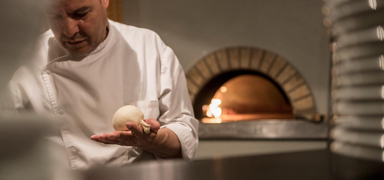 pizzaiolo prepares the pizza dough