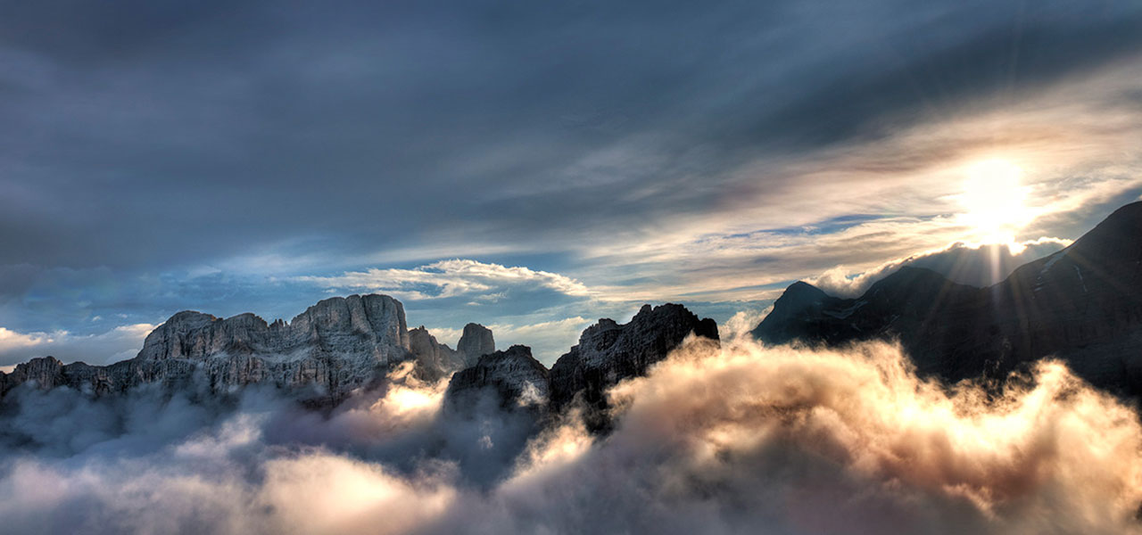 Sun flashing through the clouds over the Dolomites