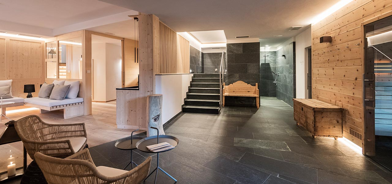 The wellness area for adults only by stone and natural wood: shower, cold water bath tube and sofas in the lounge area