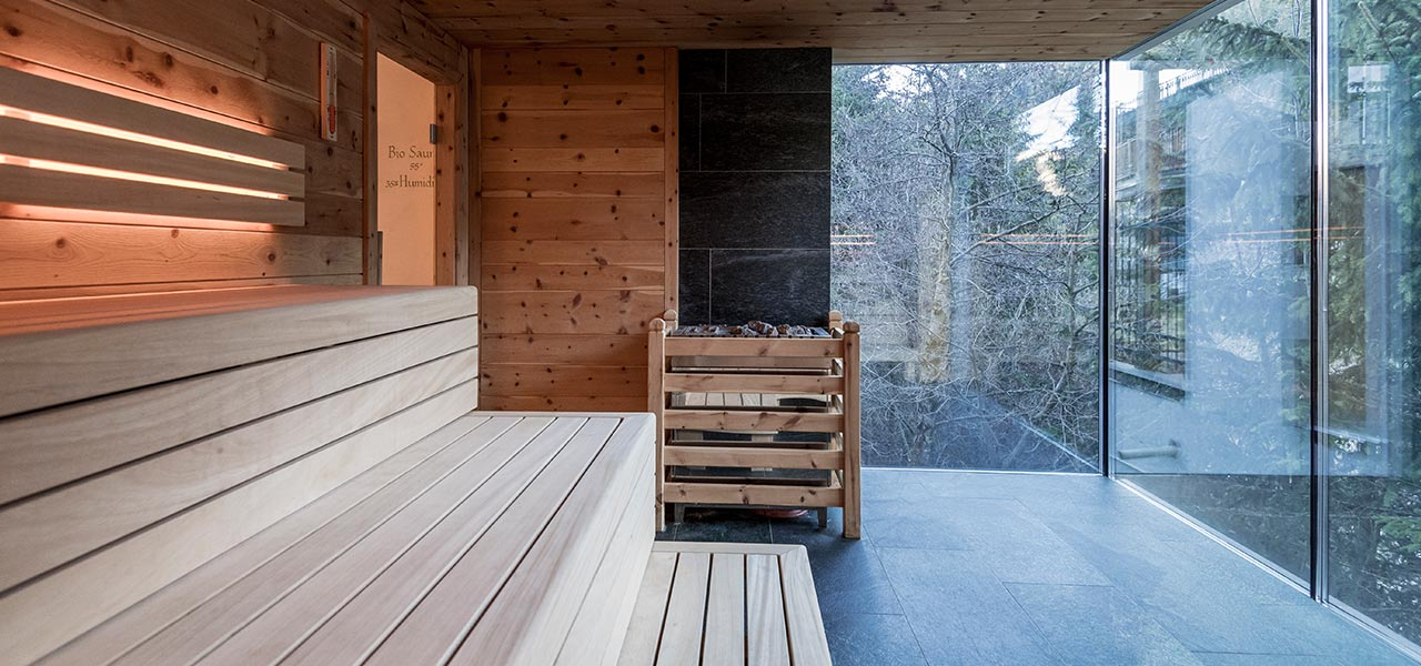 Wooden bench, natural stone flooring and large windows inside the sauna at Rosa Alpina