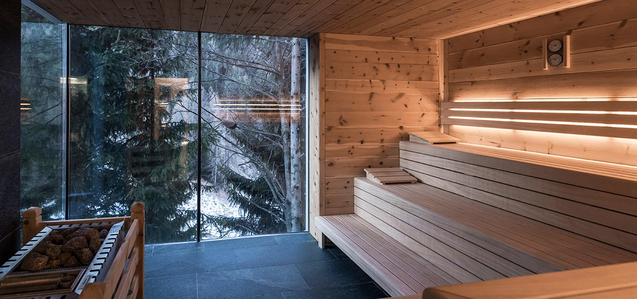Interior of a Finnish sauna with glass wall overlooking a wood