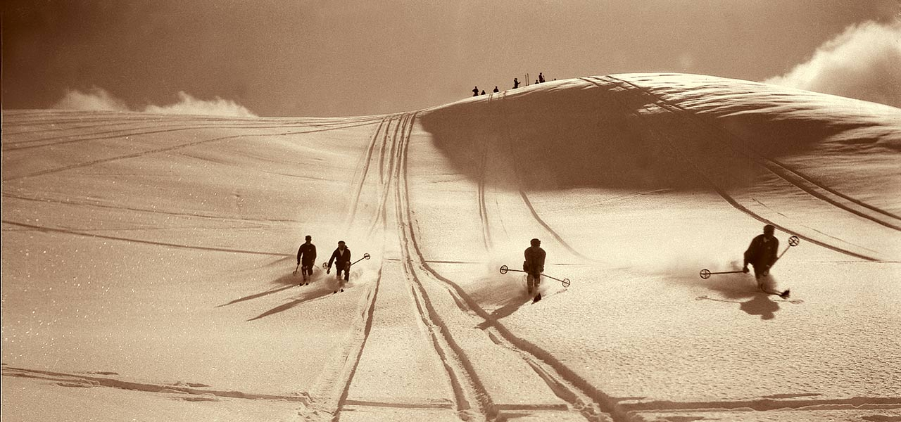 Historical sepia picture of skiers on a slope