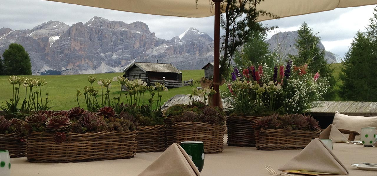 Decorated table with view of mountain hut and Dolomites
