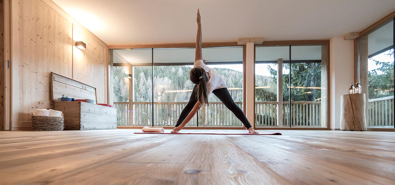 Girl practicing stretching exercises in the natural wood Yoga Studio with wide windows at Rosa Alpina Hotel